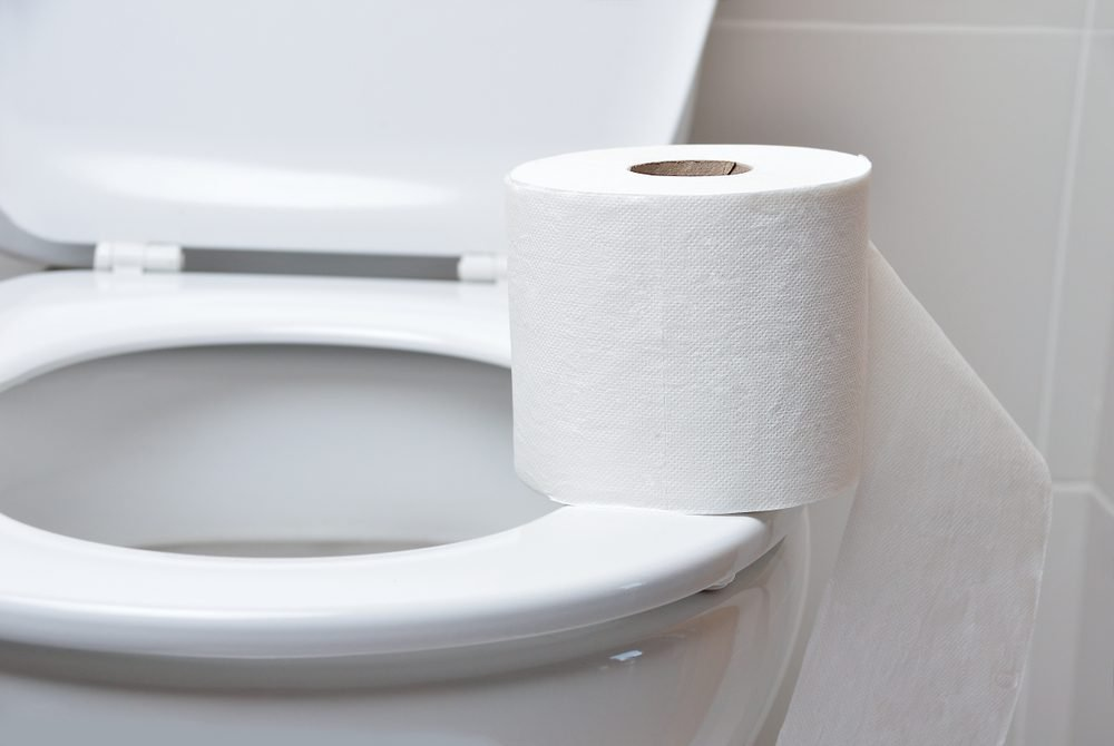 Toilet paper on a toilet with the lid open