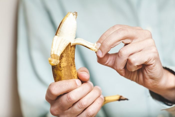 Male hand in a shirt holding a ripe banana and clean it