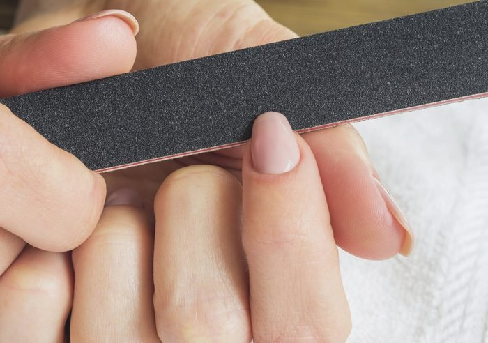 Female hands manicure with nail file.