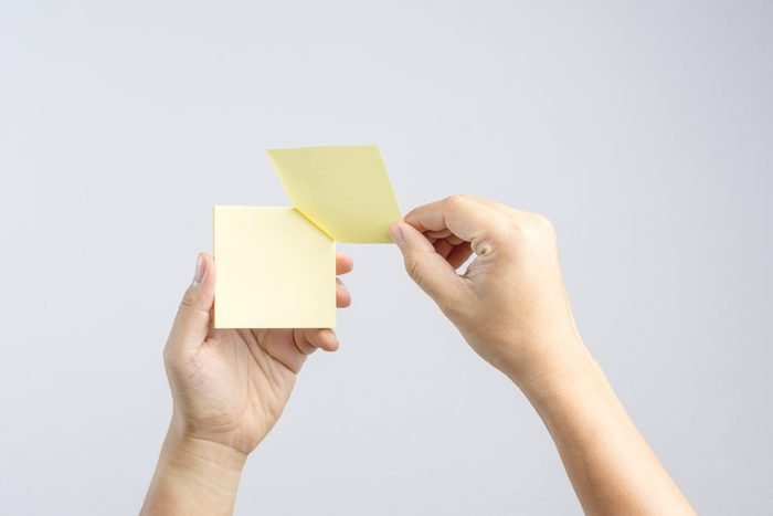 Hand holding sticky post note paper sheet on white background