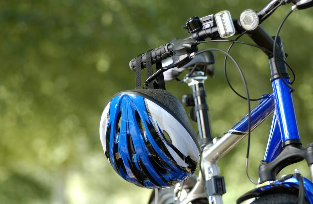 Blue bike and blue helmet in park with trees