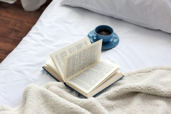 Open book and cup on bad close-up