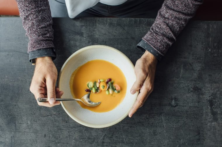 Hands of unrecognisable man eating a soup at restaurant.