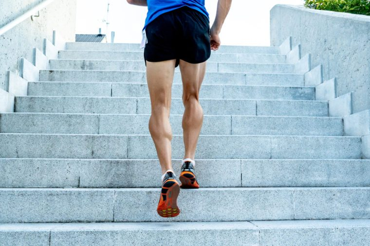 Close up of young runners legs running up the stairs in running clothes