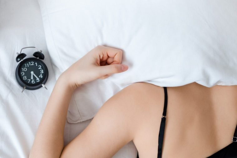 Young woman with pillow over her head with alarm clock on bed in the morning. Student or schoolgirl do not want to wake up early for school or univercity. Oversleep, not getting enough sleep concept.