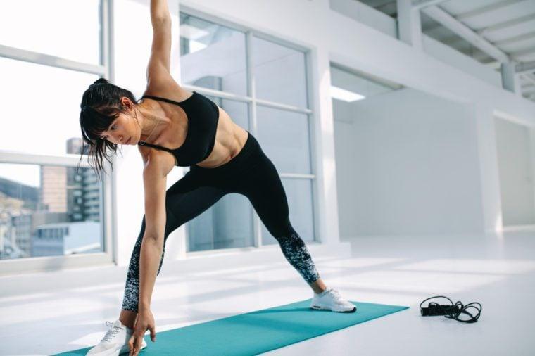 Fitness woman in Utthita Trikonasana pose at gym. Female with slim figure practising yoga workout in fitness studio.