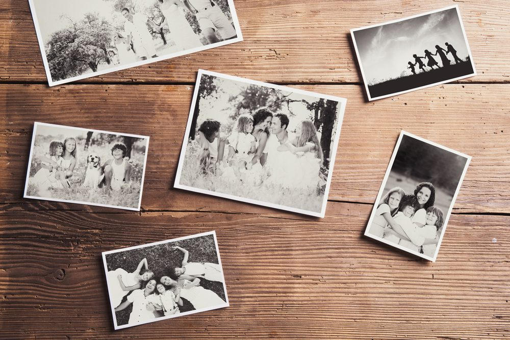 Black and white family photos laid on wooden floor background.