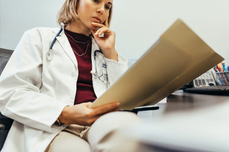 Doctor reading medical documentation in hospital. Female physician sitting in her office and examining medical records.