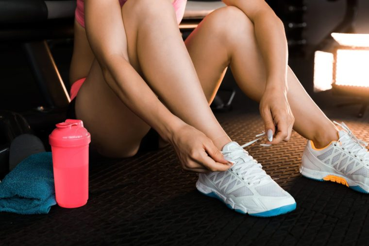 woman tying shoelaces of white sneakers siting on a mat surrounded by mobile phone, earphones, towel and a shaker in the gym. Concept of smart digital sport