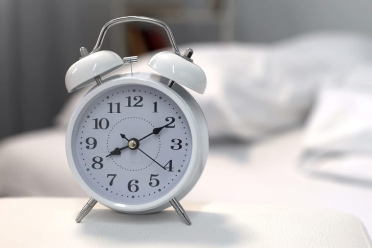 Alarm clock showing morning time on night table near bed, sleeping hours