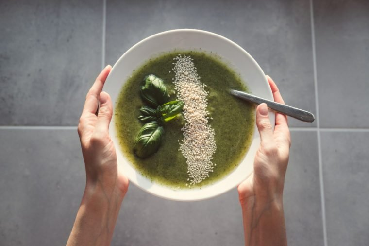 Fresh green healthy vegan soup in woman's hands on a grey tile background. Overhead shot of fresh soap in the hands. Broccoli soup with basil.