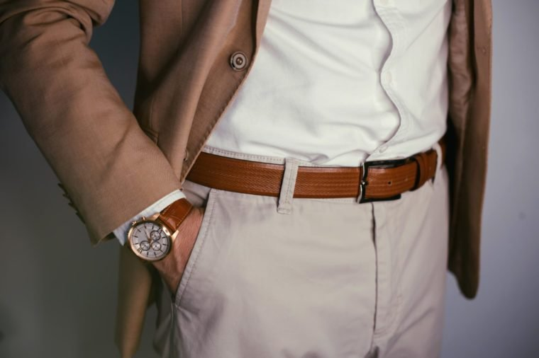 Closeup fashion image of luxury watch on wrist of man.body detail of a business man.Man's hand in beige pants pocket closeup at white background.Man wearing brown jacket and white shirt.Not isolated