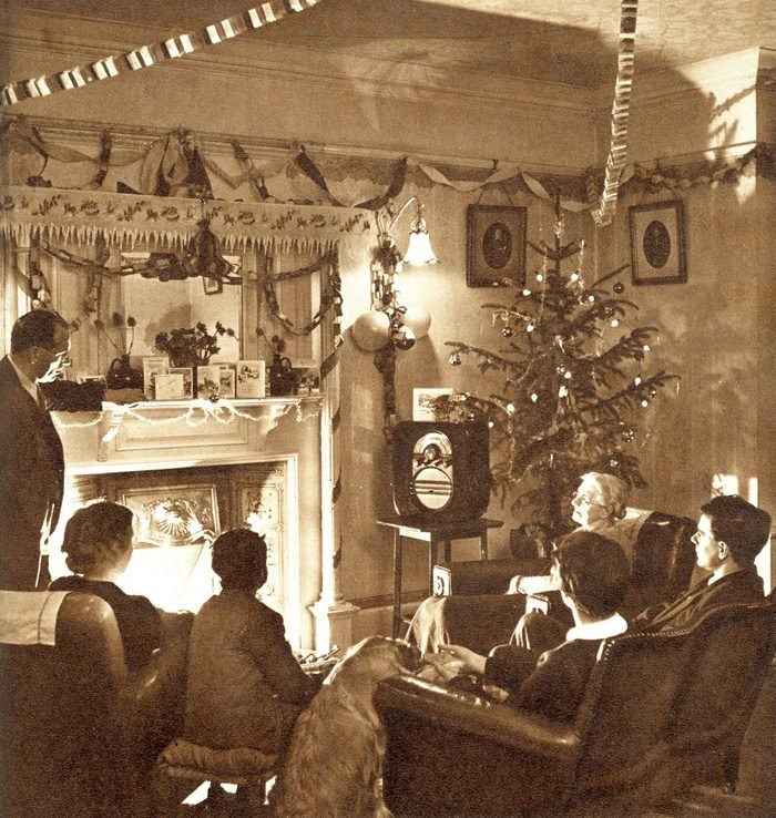Mandatory Credit: Photo by Historia/Shutterstock (9831785a) A 1950s Family Sit Around the Fire at Christmas Time Listening to A Wireless Broadcast Streamers and Paper Chains Hang From the Ceiling and A Rather Mean Looking Christmas Tree Stands in the Corner. . Photograph by Sketch Special Photographer, Harold White, the Sketch, 31 December 1952 Christmas 1952 by Harold White, 1952
