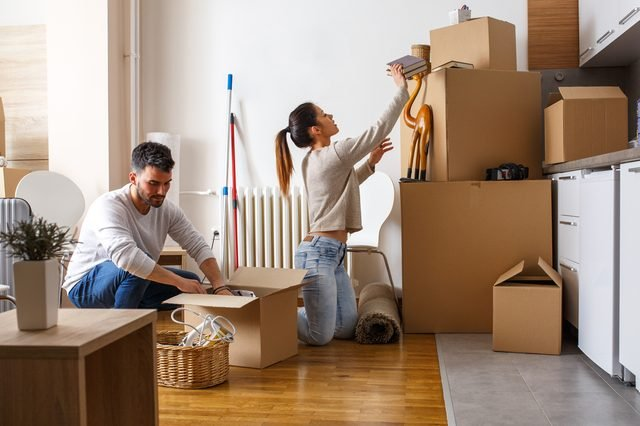 Young couple unpacking cardboard boxes at new home.Moving house.Real estate.