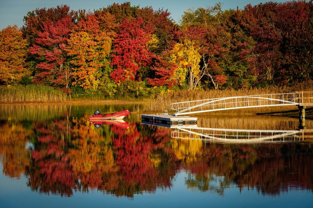 Dinghy on lake with fall foliage near Kennebunkport, Maine in autumn