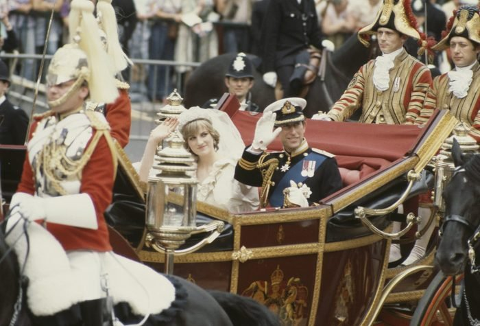 Charles, Prince of Wales, and his wife, Princess Diana (1961 - 1997), wave to the crowds following their wedding ceremony