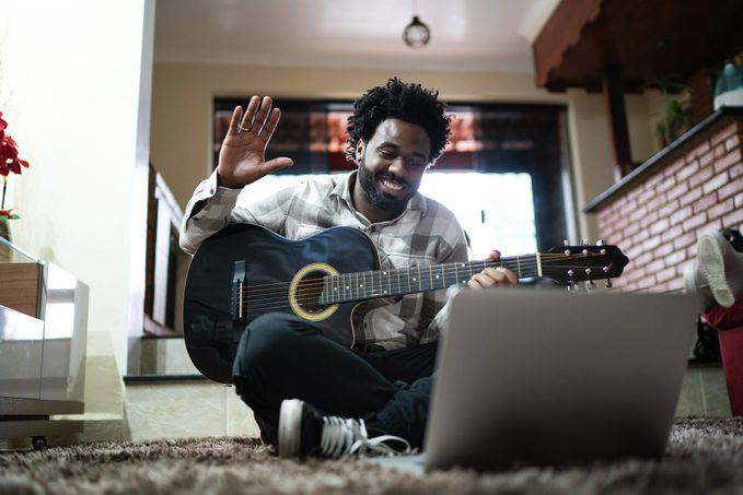Acoustic Guitar Teaching Through A Video Call, Waving To Laptop At Home