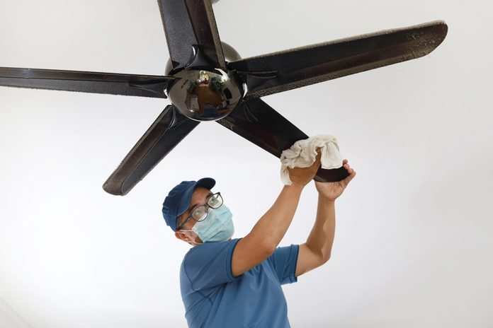 Asian Man Wearing A Protective Mask Cleaning Ceiling Fan At Home