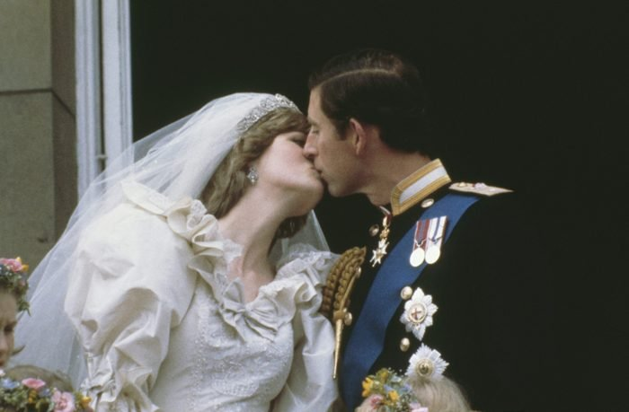 Prince Charles, Prince of Wales, kissing his wife, Princess Diana (1961 - 1997), on the balcony of Buckingham Palace in London after their wedding
