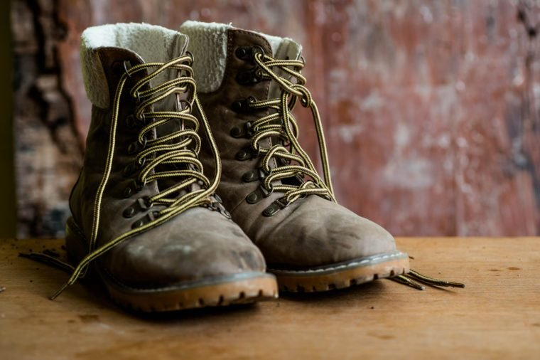 A pair of dirty boot on wooden background