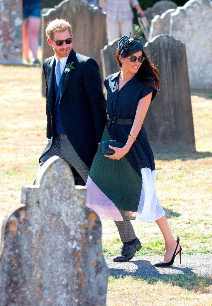 Meghan Duchess of Sussex with clutch in front of stomach