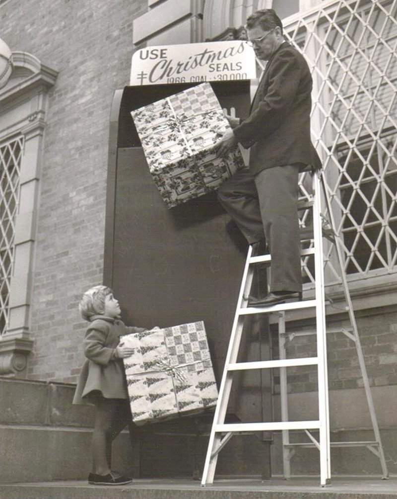 This is me at three years old during Christmastime in 1966 Modesto; CA. I wish this was in color as my coat was bright red! This was on the steps of the Modesto Post Office where I was with my mom when I saw a man lifting packages and ran up to help him and a photographer snapped this picture! Turned out he was making a display for Christmas Seals...not actually putting packages in the big box! And they ended up using it for their fundraising campaign!