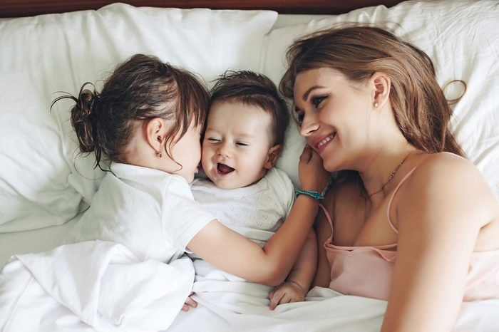 Young mom with her 5 years old daughter and 4 months old baby dressed in pajamas are relaxing and playing in the bed at the weekend together, lazy morning