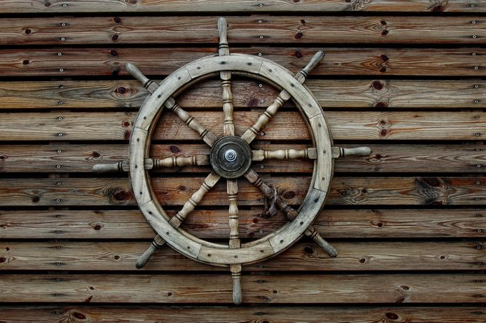 Steering wheel of the ship on a wooden wall of restaurant in marina of Tel-Aviv (Israel)
