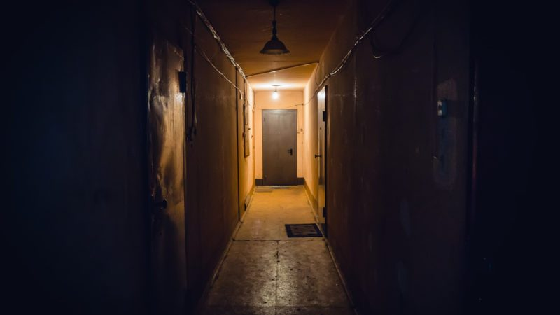 Dirty empty dark corridor in apartment building, doors, lighting lamps, perspective, in yellow-orange tones, copy space