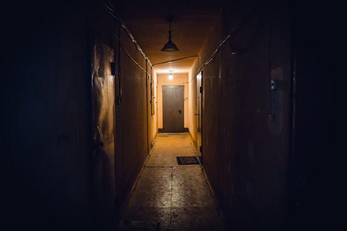 Dirty empty dark corridor in apartment building, doors, lighting lamps, perspective, in yellow-orange tones, copy space