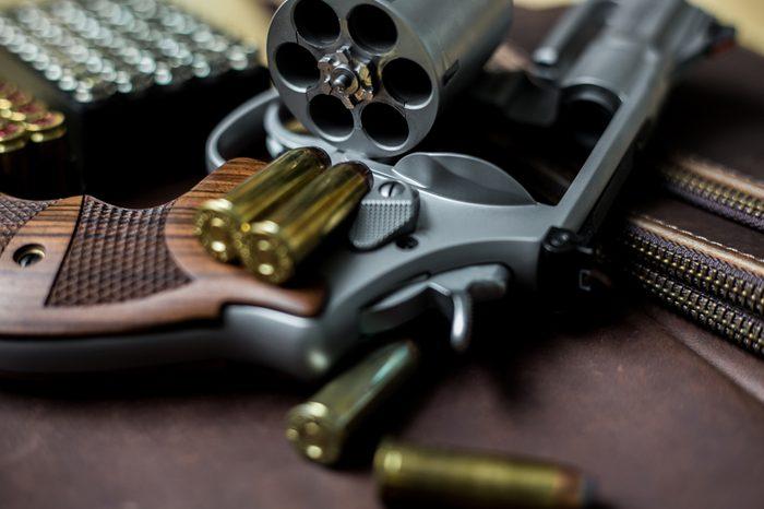 Revolver .44 magnum gun with jacket soft point (JSP) 240 grain bullet on leather background