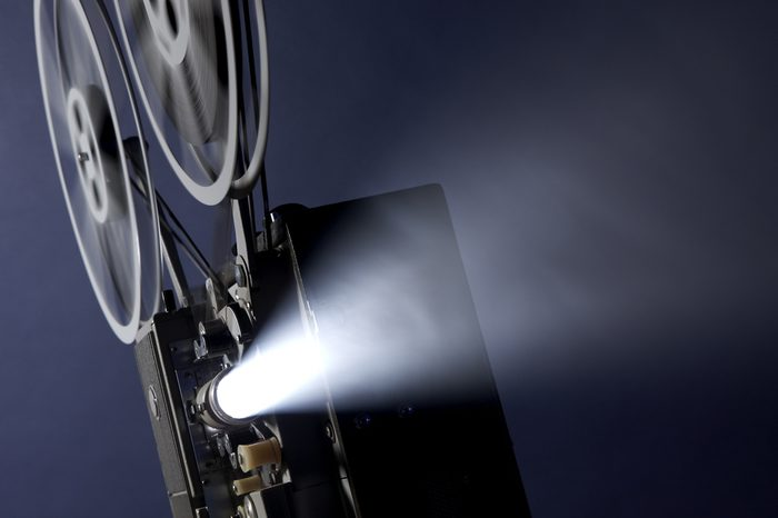 Angled 16mm movie projector projecting images through smoky background with space for copy