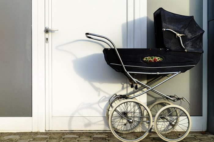 Retro style stroller baby carriage outdoors near house door