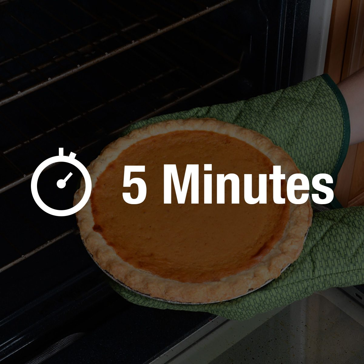Closeup of a woman taking a fresh baked pumpkin pie from the oven