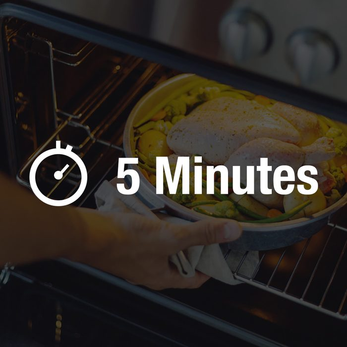 Cook putting raw chicken with vegetables to the oven.