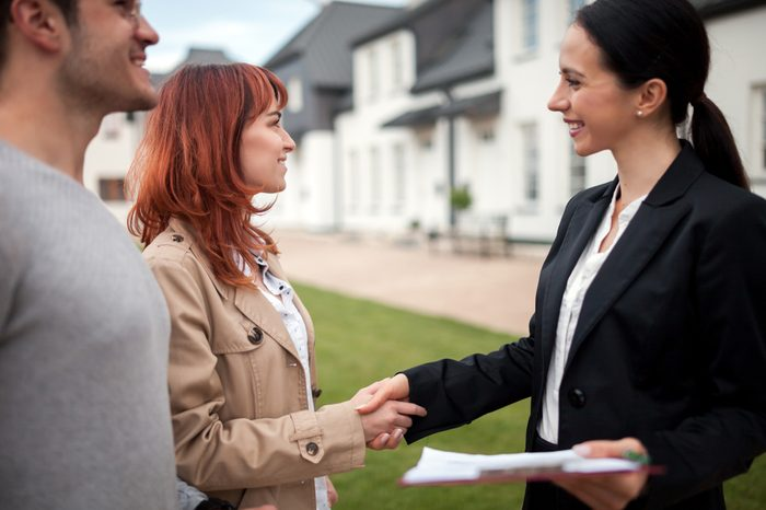 Real estate agent shaking hands with customers after buying new house in residential area