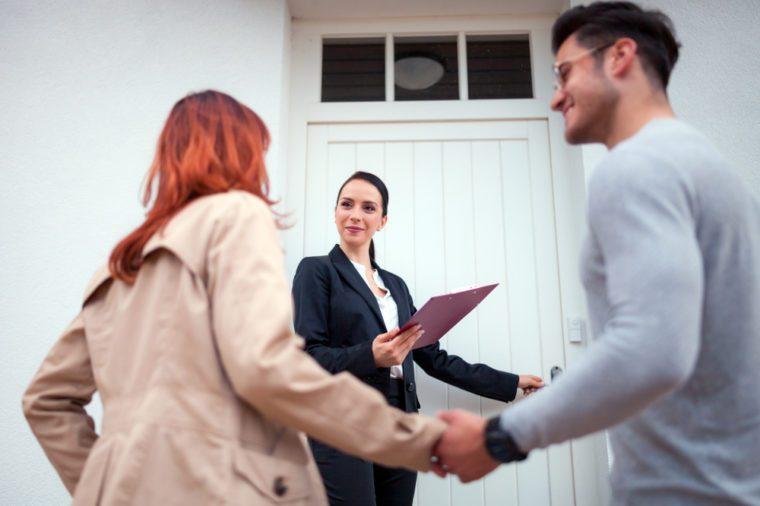 Real estate agent near door inviting young couple to enter house for visit