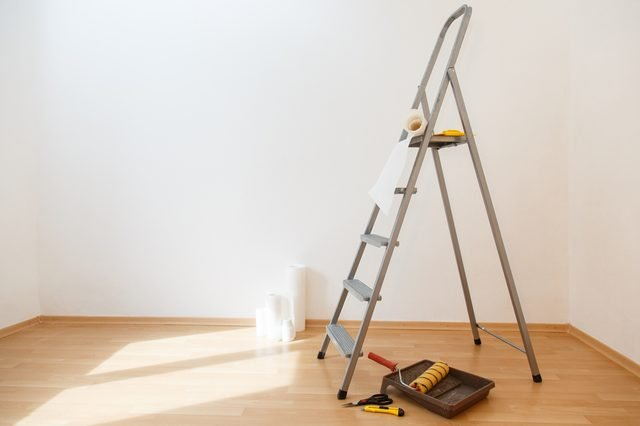 Wallpaper gluing in a room. Tools for gluing white wallpapers. White room after renovation. Fresh repair in a room
