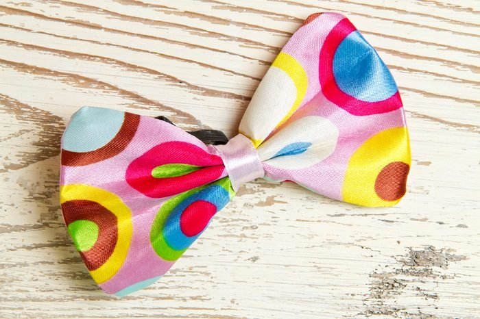 Funny, colorful bow tie on white wood