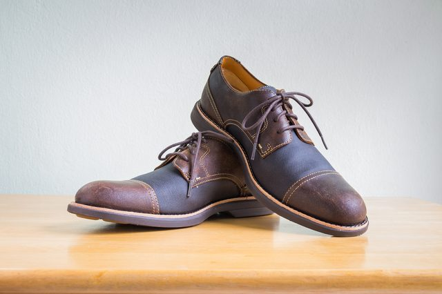 Men's accessories with brown leather shoes on wooden table, bar or counter over gray wall background