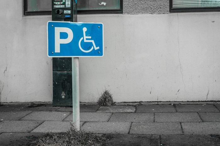 Handicap parking sign on a street in front of a building