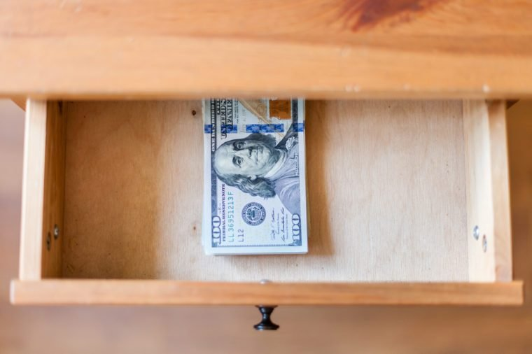 top view of hundred-dollar bills pack in open drawer of nightstand