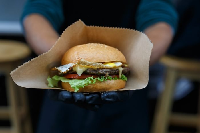 Fresh burger cooked at barbecue outdoors in craft paper. Cookout american bbq. Big hamburger with steak meat and vegetables closeup with chef unfocused at background. Street food, fast food.