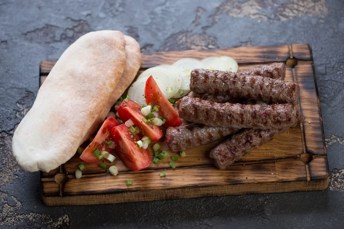 Wooden serving tray with grilled balkan cevapi, pitas, tomatoes and onion, studio shot