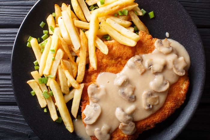Jaeger Viennese schnitzel with French fries and mushrooms close-up on a plate. horizontal top view from above