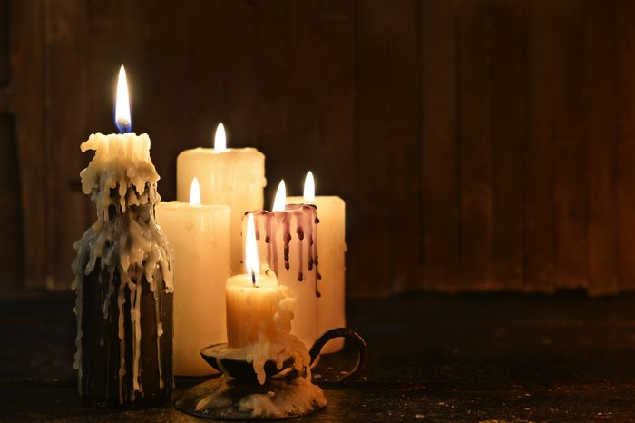 Group of evil candles burning in the darkness and copy space on wooden background. Black magic ritual or scary halloween rite.