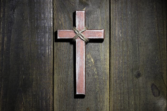 Spotlight on hanging wooden cross on old rustic antique wood background; Easter, Christmas, Memorial Day and religious background with copy space