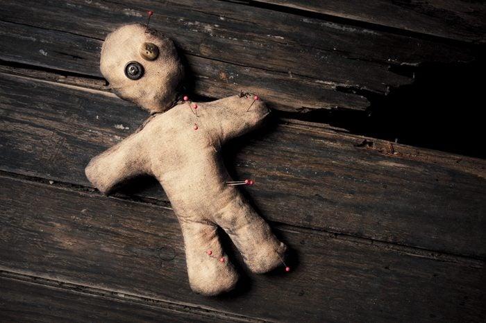 photo of creepy voodoo doll on wooden floor