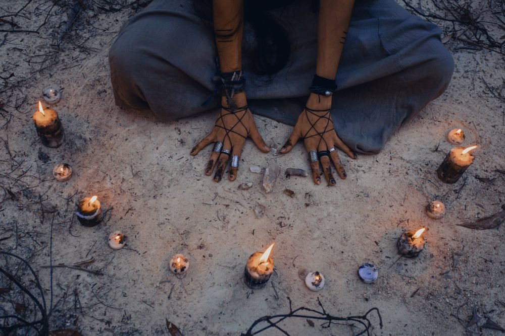 Witchs hands from above with candles deep in forest.
