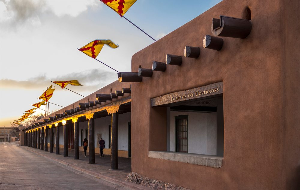 Flags flying above the Palace of the Governors, Santa Fe Plaza, State Capital of New Mexico at sunset on a spring evening. Adobe structure and historical Spanish seat of government in the Southwest.